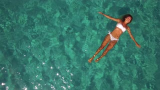 aerial-woman-floating-in-crystal-clear-water